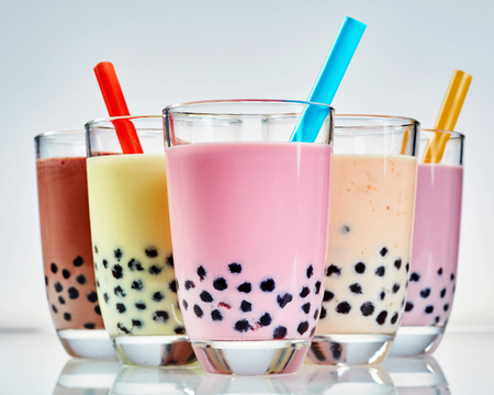 Five glasses of healthy milky boba or bubble tea flavored with fresh fruit and chocolate and served with traditional wide straws Imagens
