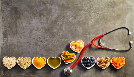Healthy heart food concept with a row of heart-shaped dishes with oats, salmon, turmeric, lentils, peppers, olive oil, acai, walnuts and carrot forming a border with a stethoscope on copy space