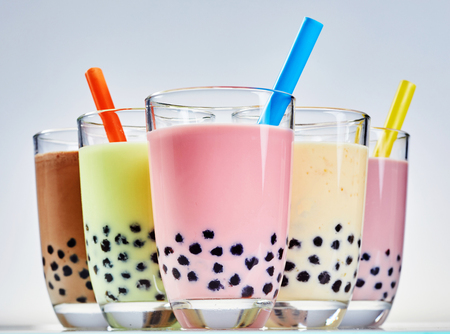 Glasses of fruity bubble or boba Asian tea with tapioca balls or pearls and milk served with wide straws in assorted flavors