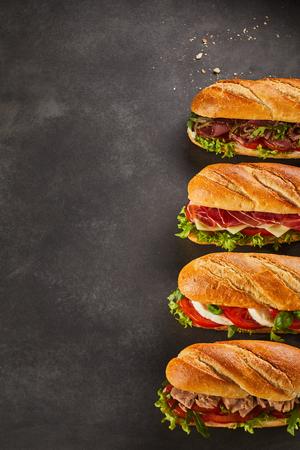 4 完全なサンドイッチのセットはコピー スペースと暗い背景上盛り合わせ肉のスライスと野菜いっぱい 写真素材