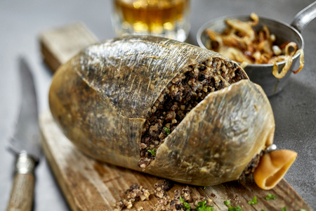 Carved haggis showing the internal texture of the savory offal mixture on a wooden cutting board with focus to the meat conceptual of traditional regional Scottish cuisine
