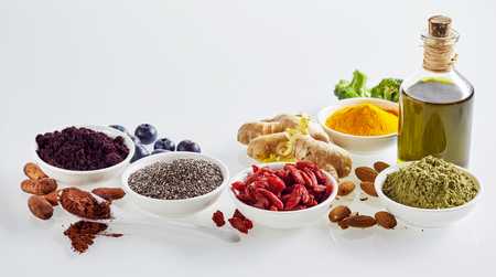 Panoramic banner of healthy superfoods on white for a healthy diet and heart with acai, cacao, goji, chia seeds, turmeric, curcuma, ginger, olive oil, broccoli and almonds with copy space