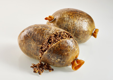 Haggis filled with minced meat and partially open to display contents over white background Imagens