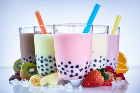 Refrescante té helado de leche con perlas de tapioca hecho con ingredientes de fruta fresca, como frambuesa, fresa, kiwi, naranja, manzana y plátano Foto de archivo - 76733137