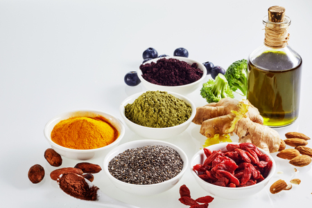 Arrangement of superfoods for a healthy diet and heart with acai, cacao, goji, chia seeds, turmeric, curcuma, ginger , broccoli, almonds and extra virgin olive oil on white with copy space
