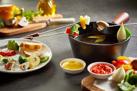 Tasty healthy vegetarian fondue with farm fresh vegetables served with dipping sauces and crusty baguette bread