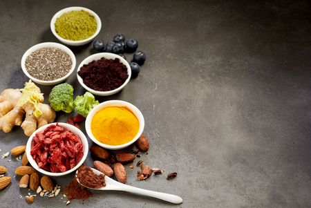 Selection of superfoods for a healthy diet and heart with acai, cacao, goji, chia seeds, turmeric, curcuma, ginger and almonds arranged as a border on textured grey with copy space