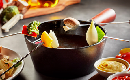 Healthy vegetable fondue with fresh produce including sweet bell peppers, onion or shallots, broccoli and mushrooms served with dipping sauces to be cooked in hot oil