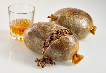 Sliced open cooked Scottish haggis with a tumbler of whisky, a traditional meal for Robert Burns Supper