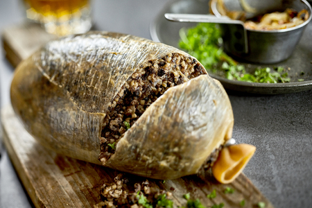 Traditional cooked Scottish haggis with chopped fresh herbs on a wooden hopping board cut through to show the texture of the meat