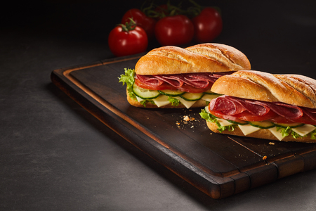 Two pepperoni sandwiches with cheese and cucumber on dark wooden cutting board. Tomatoes and copy space around them.