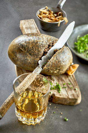 Cooked haggis sliced through with a carving knife on an old wooden board served with a glass of Scotch whisky