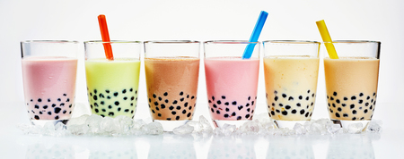 ice crushed: Traditional Asian milky bubble tea with tapioca pearls flavored with fresh fruit, caramel and chocolate in a line in panoramic banner format