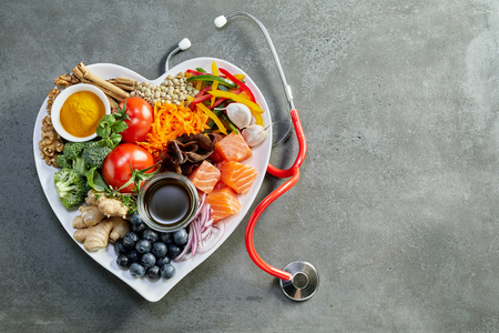 Fresh food for a healthy heart with acai, lentils, soy sauce, ginger, salmon, carrot, tomato, turmeric, cinnamon, walnuts, garlic, peppers, broccoli, basil, onion with a stethoscope and copy space