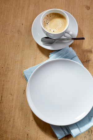 energising: Cup of coffee on a saucer and empty white plate on blue napkin served over wooden table, from above studio shot Stock Photo
