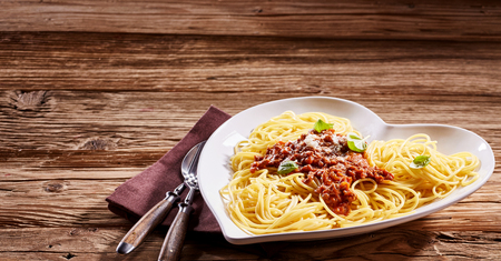 Serving of tasty Italian spaghetti in a heart-shaped dish on a rustic wooden table in panoramic banner format with copy space