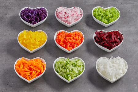 Little heart-shaped white bowls with grated vegetables of different colors. Healthy food diet studio shot concept