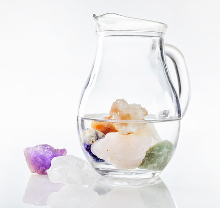 complementary therapies: Transparent glass jug of drinking water with submerged healing stones and colorful minerals, isolated on white background