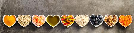 健康的な食材は、小さなハートのボウル、バナーのワイド フレームでトリミング灰色の背景の上に上から撮影スタジオの長いストレートの行に配置