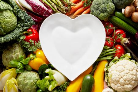 白い空ハート型プレート中新鮮な野菜の山の上。コピー スペースでカラフルな有機食品コンセプト