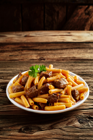 ridged: Beef rigatoni noodles served on a white dish on a rustic wood counter with copy space in a concept of healthy Mediterranean and Italian cuisine Stock Photo