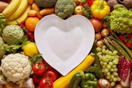 Empty white heart shaped plate in the middle of full frame shot among fresh colorful vegetables and fruits surrounding it all over the table, overhead studio shot Banco de Imagens