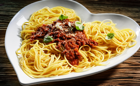 carne picada: Heart-shaped dish of tasty Italian spaghetti bolognese topped with a tomato and minced beef sauce, parmesan cheese and fresh basil on a rustic wood background