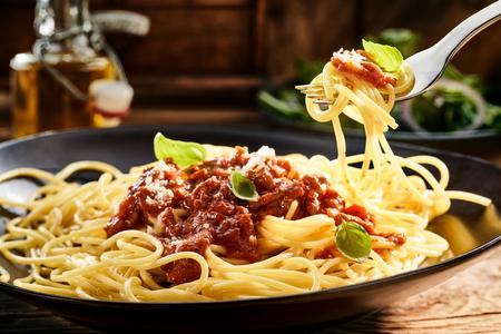 おいしいイタリアのスパゲッティ バジルとパルメザン チーズ添え上記フォークにくるくる一口牛肉とトマトのソースをトッピングのプレートを食べ