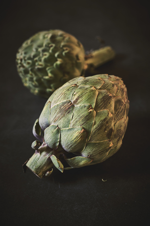 Fresh uncooked globe artichokes rich in antioxidant formed from the immature bulb of a Mediterranean thistle ready for cooking with copy space below Banco de Imagens