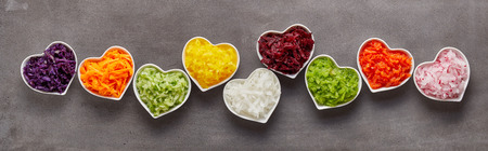 Healthy grated vegetables of different colors in heart-shaped bowls in funny long row as wide banner concept Reklamní fotografie