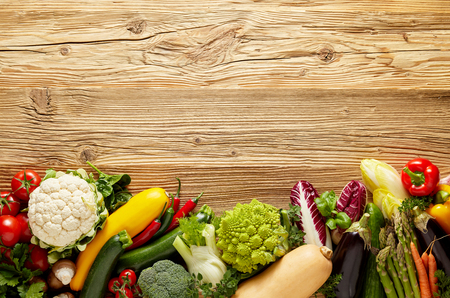 Row of fresh vegetables on bottom of the frame - background concept with rough wooden table surface for copy space