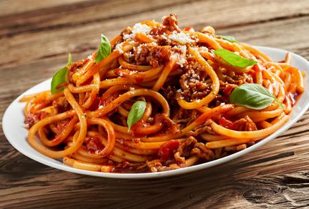 Plaat van smakelijke pittige Italiaanse spaghetti Bolognese met gehakt, verse basilicumbladeren en een besprenkeling van Parmezaanse kaas