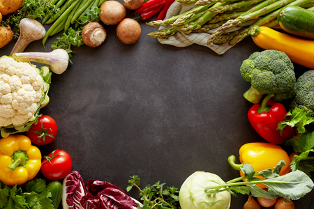 Healthy food background concept with fresh vegetables forming colorful frame around empty copy space of black chalkboard background in the middle, studio shot from above