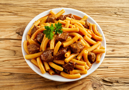 ridged: Plate of Italian rigatoni pasta with sauce and diced lean beef garnished with parsley viewed from overhead on a rustic wood background