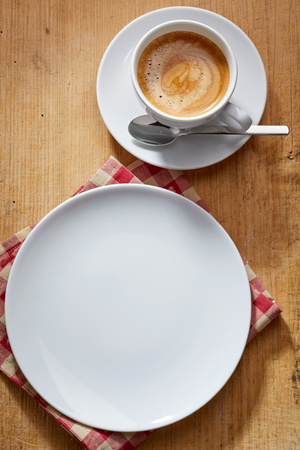 energising: Empty white plate served over red napkin and cup of coffee with spoon on a saucer served over rustic wooden table, studio shot from above