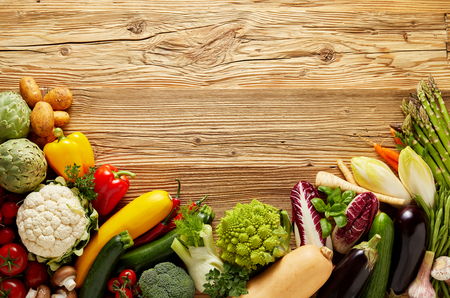 Studio photo of fresh vegetables placed on the bottom of the frame with copy space on rough woodgrain background Stock Photo