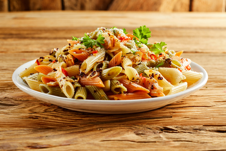 ridged: Plate of wholewheat and semolina mixed penne pasta in a spicy sauce with seasoning and parsley served on a white dish on wood for healthy vegetarian and Italian cuisine