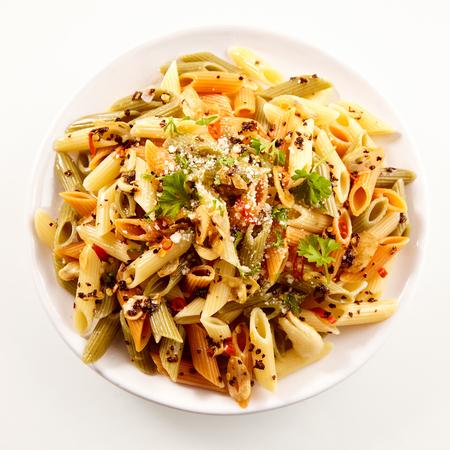 スパイスとハーブの正方形フォーマットで白い板の上から見たイタリア ベジタリアン全粒粉ペンネ パスタのおいしい料理