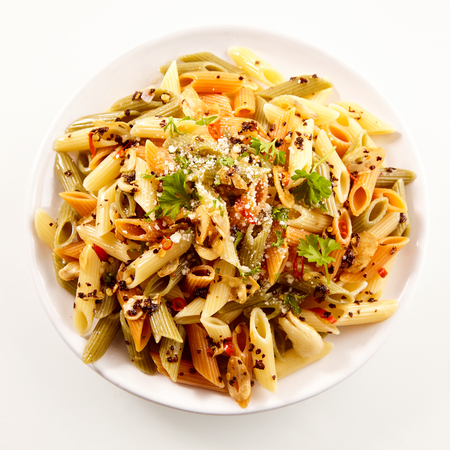 Tasty dish of Italian vegetarian wholewheat penne pasta with spices and herbs viewed from the top on a white plate in square format