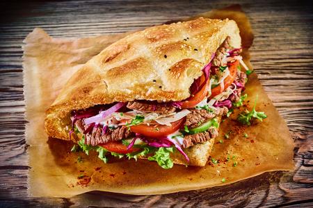 소박한 종이와 나무에 신선한 샐러드 재료와 함께 제공되는 전통적인 수직 rotisserie 떨어져 구운 된 구운 고기와 함께 피타 빵에 맛있는 터키어 doner 케