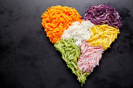 Heart shaped pile of grated vegetables as ingredients for cooking placed over black surface background with copy space. Healthy organic food concept Banco de Imagens - 77198126