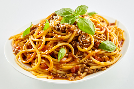Spaghetti noodles with Bolognese sauce and fresh basil sprinkled with parmesan cheese for traditional Italian cuisine Imagens