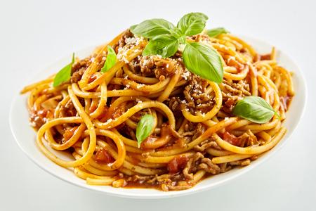Spaghettinoedels met Bolognese saus en verse basilicum bestrooid met parmezaanse kaas voor de traditionele Italiaanse keuken
