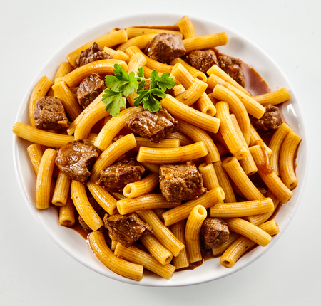 Tubular rigatoni Italian noodles with beef served in a spicy sauce garnished with parsley viewed from above in square format Banco de Imagens