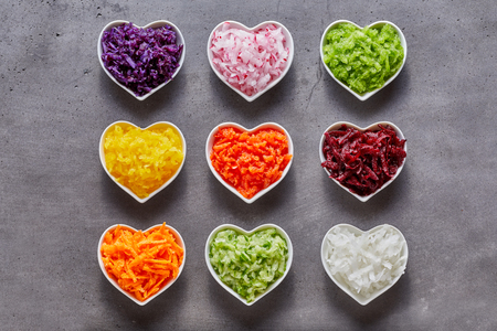 Heart-shaped bowls with healthy grated vegetable ingredients of different colors shot from above on grey background Stock Photo - 77253532