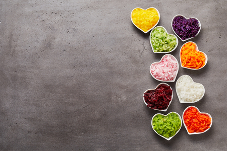 Vertical row of colorful heart-shaped bowls of grated vegetables and lots of grey metal surface for copy space to the side, studio shot made from above Imagens - 77253566