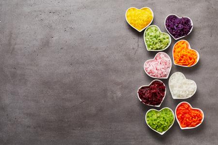 Verticale rij van kleurrijke hartvormige kommen geraspte groenten en veel grijs metalen oppervlak voor kopie ruimte aan de zijkant, studio shot gemaakt van bovenaf Stockfoto