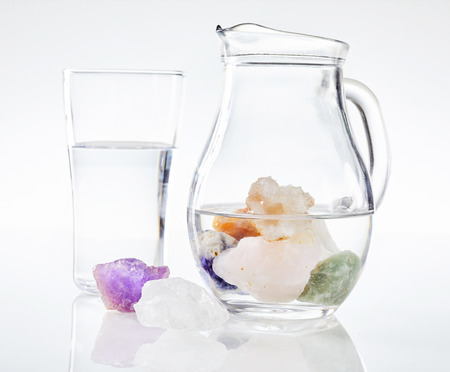 Colorful healing stones and minerals in jug of water, isolated on white background. Drinking water alternative medicine concept