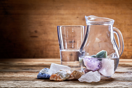 Healing stones, colorful marble minerals in transparent water in glass jug and on rough wooden table surface. Alternative medicine concept with copy space Imagens - 77253568