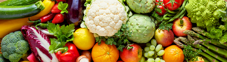 Panoramic wide organic food background concept with full frame pile of fresh vegetables and fruits mix forming bright colorful image
